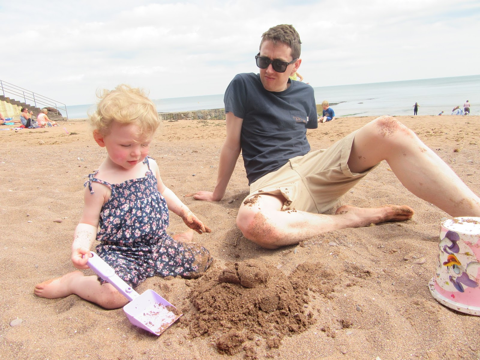Daddy and daughter building sand castles