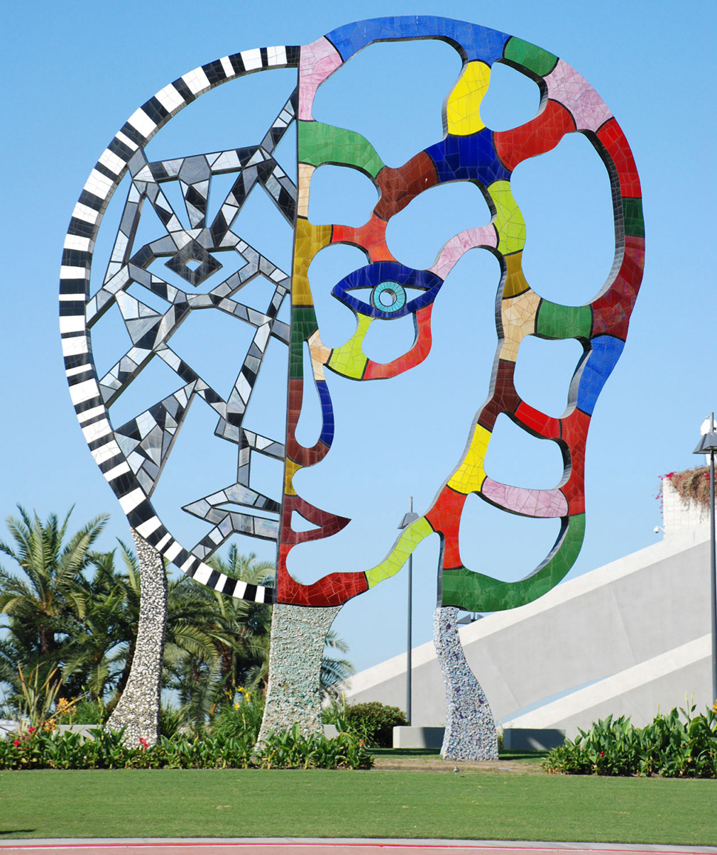 Photo of a monumental sculpture of a face by by Niki de Saint Phalle represented a face covered in black and white mosaic on one side and in brightly coloured tiles on the other.