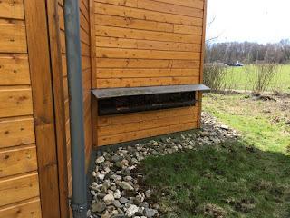 Eine Holzhütte mit länglichen Öffnungen, in die Bienen fliegen