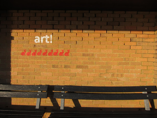 'ART' and red rabbits stencilled onto brick wall in shelter with benches