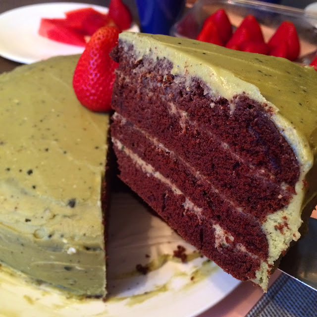 A slice of chocolate cake with matcha buttercream being lifted. The slice shows the four layers of cake with matcha buttercream between each layer.