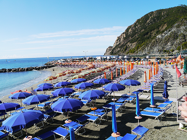 Open umbrellas on the beach on a sunny day in Monterosso al Mare, Cinque Terre, Italy