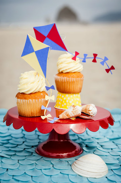 Beach party cupcakes with kites as toppers. Visit www.fizzyparty.com for more inspiration