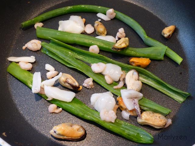 Placez tige d'oignon nouveau et fruits de mer dans une sauteuse.