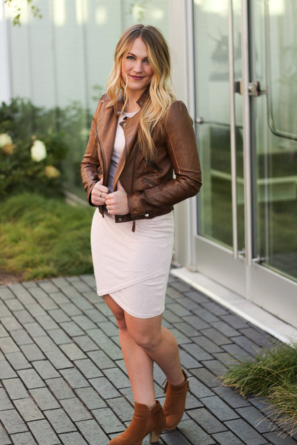 young woman sporting a tan moto jacket over a pink dress with fringe booties
