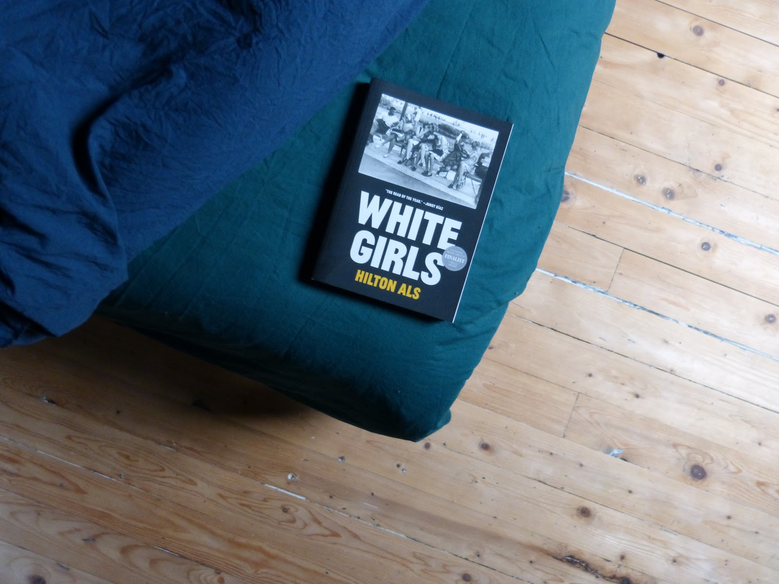 The picture shows the corner of a bed, covered in a green sheet and with a blue sheet folded over. On the 'exposed' green sheet lies a book (White Girls by Hilton Als). The rest of the picture shows the wooden floor the bed is standing on.