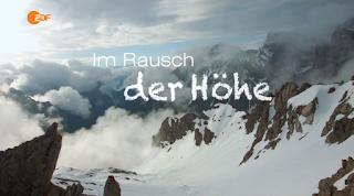 """Im Bild ist ein verschneites Gebirge zu sehen. Das Bild ist aus einem Helikopter entstanden. Zwischen den Gipfeln sind vereinzelt Wolken zu sehen, in der Bildmitte steht """"im Rausch der Höhe"""""""