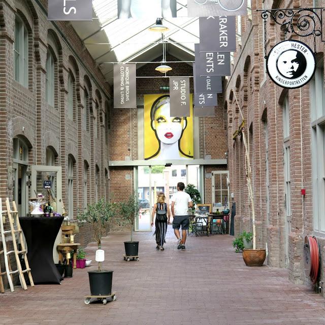 מסדרון וסביבו חנויות בוטיק במתחם foodhallen  באמסטרדם