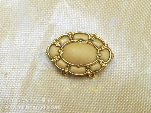 The oval stamping is now placed on to the epoxy clay and pressed in so that it forms little cushions in each of the open spaces of the filigree.