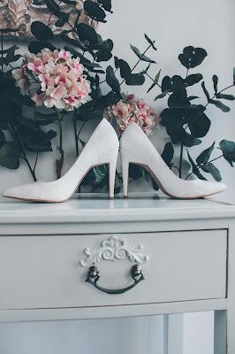 Zapatos blancos de novia sobre una cómoda