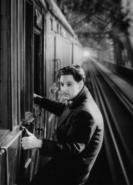 Robert Donat hanging on to the side of a train