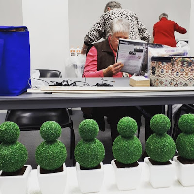 Six one-twelfth scale topiaries in planters lined up on a table. In the background is a woman reading a magazine and two women with their backs turned to the camera working on something.