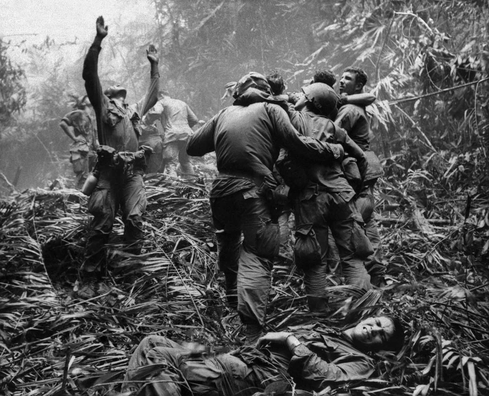 As fellow troopers aid wounded comrades, the first sergeant of A Company, 101st Airborne Division, guides a medevac helicopter through the jungle foliage to pick up casualties suffered during a five-day patrol near Hue, in April of 1968.