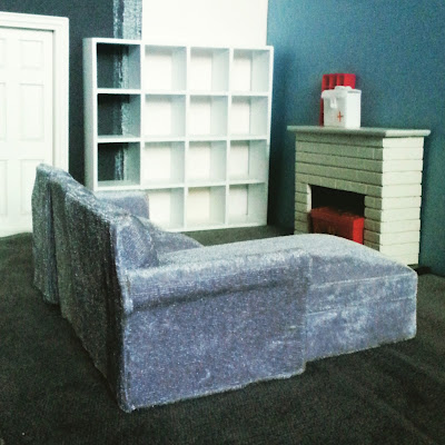 One-twelfth scale modern miniature lounge scene with a grey velvet sectional sofa in front of a fireplace.