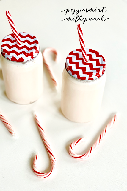 Two jars with red and white striped lids filled with a pink milk punch
