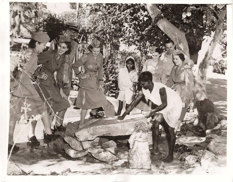 A Dhobi (Laundryman) is washing Clothes on a Stone slab and Five U.S. Army Nurses are Watching - India, 1943