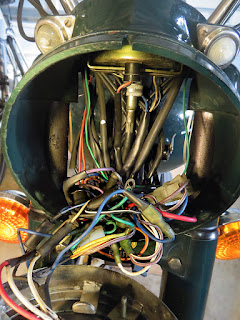Jumble of wires inside motorcycle headlight nacelle.