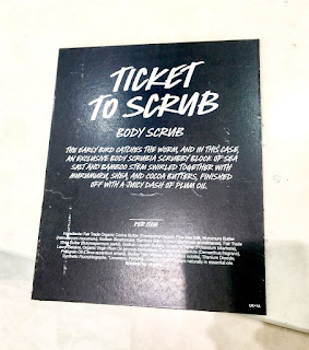 A black rectangular card with Ticket To Scrub in big white font with Body Scrub in smaller white font with very small details of the ingredients in white font on a white background