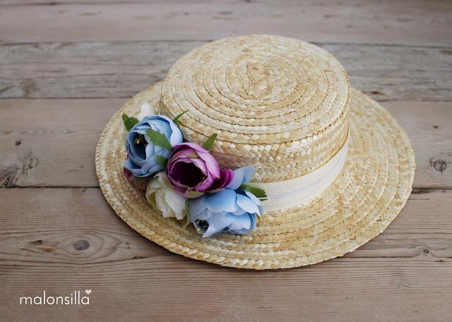 Sombrero de paja tipo canotier con flores en colores pastel apoyado sobre suelo de madera
