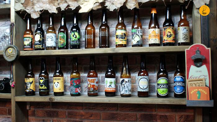 Estantería con tercios de cerveza artesana en Fogg Bar La Chula, Shizun Panda, La Quince, Mad Brewing, Freaks, La Virgen,Domus, Sevebrau, Monkey, Guineu, Naparbier