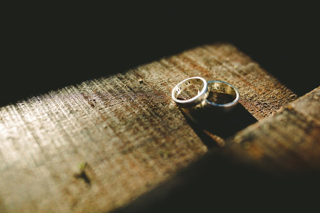 Pair of weddings rings on a wooden blog with the sun shining on them