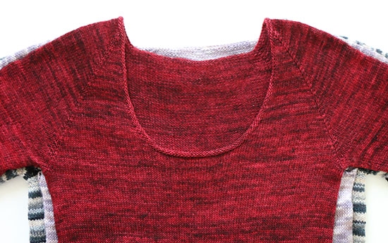 Front view of three sweaters stacked on one another, showing that they progress from narrowest to widest.