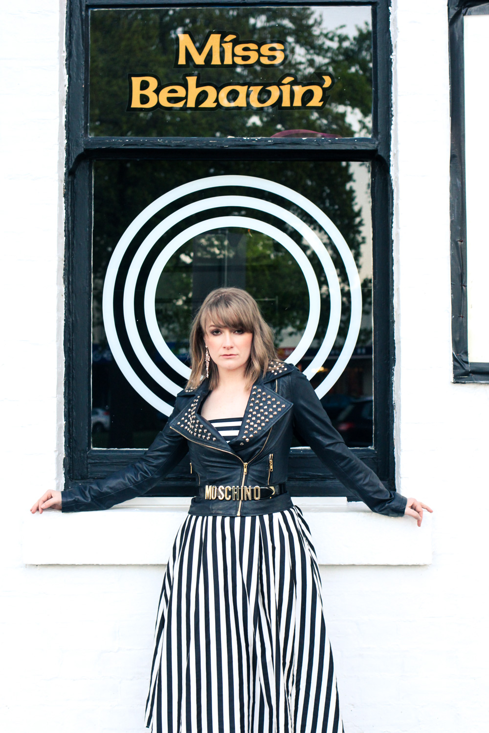 Liana of @findingfemme wears studded leather biker jacket, Moschino belt and black and white striped dress