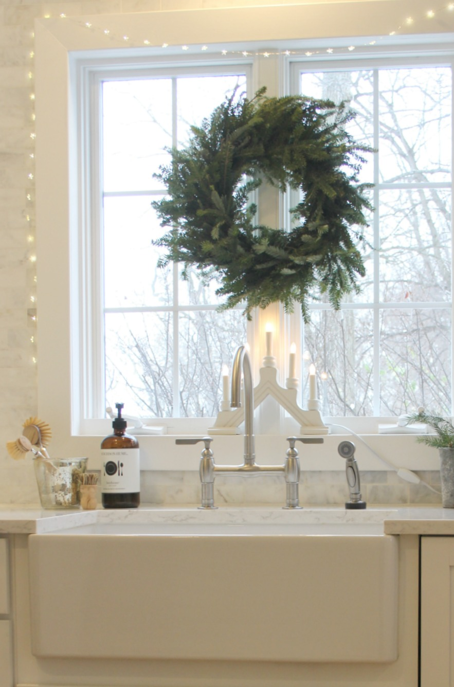 White Swedish style kitchen with farm sink and fresh wreath - Hello Lovely Studio