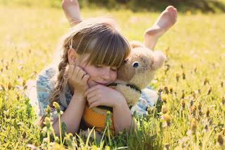 Ein kleines Mädchen liegt Glücklich mit Ihrem Kuscheltier im Gras