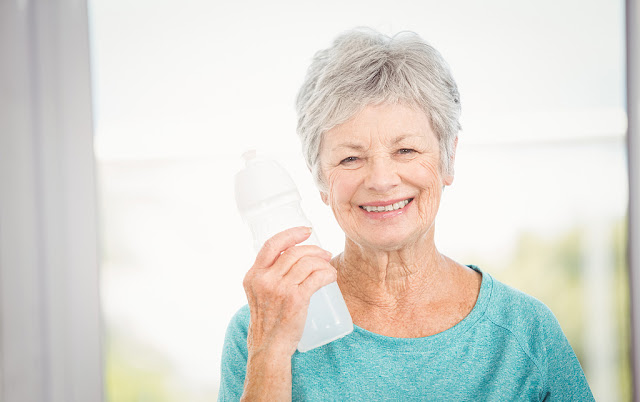 a smiling old woman holding a bottled water