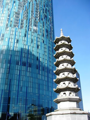 Chinese pagoda sculpture and part of skyscraper on a sunny day