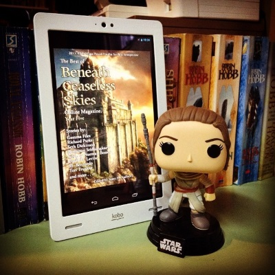 A large-headed Funko Pop bobblehead of Rey from Star Wars stands beside a white Kobo with the cover of The Best of Beneath Ceaseless Skies, Year Five on its screen. The cover features a massive castle-slash-fortress built into a cliff. The sky behind it is gold and blue.
