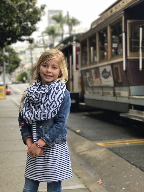 A little girl smiles in front of a Cable Car in San Francisco