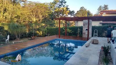 Piso da piscina com pedra São Tomé serrada branca tamanho 47 x 47 com a pedra da borda da piscina boleada na construção da piscina com o deck de madeira, o pergolado de madeira, a parede de pedra madeira para a fixação do forno de pizza em casa em Vinhedo-SP.