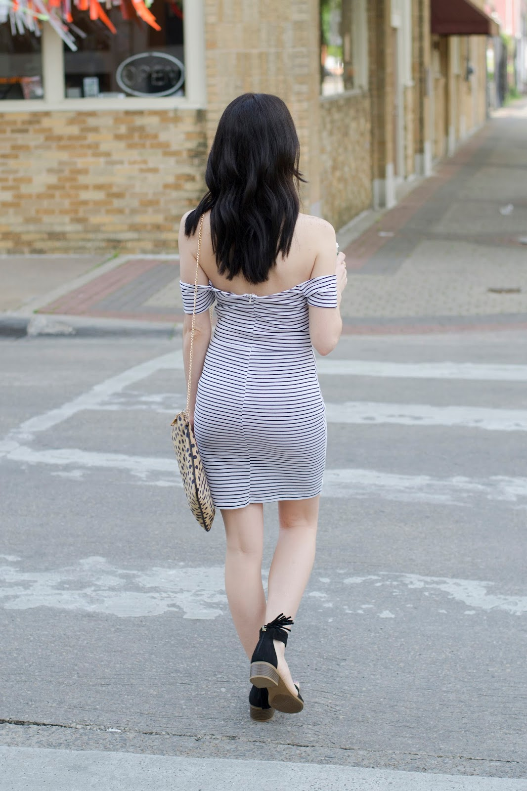 Walking across the street in black tassel sandals and short off the shoulder striped dress