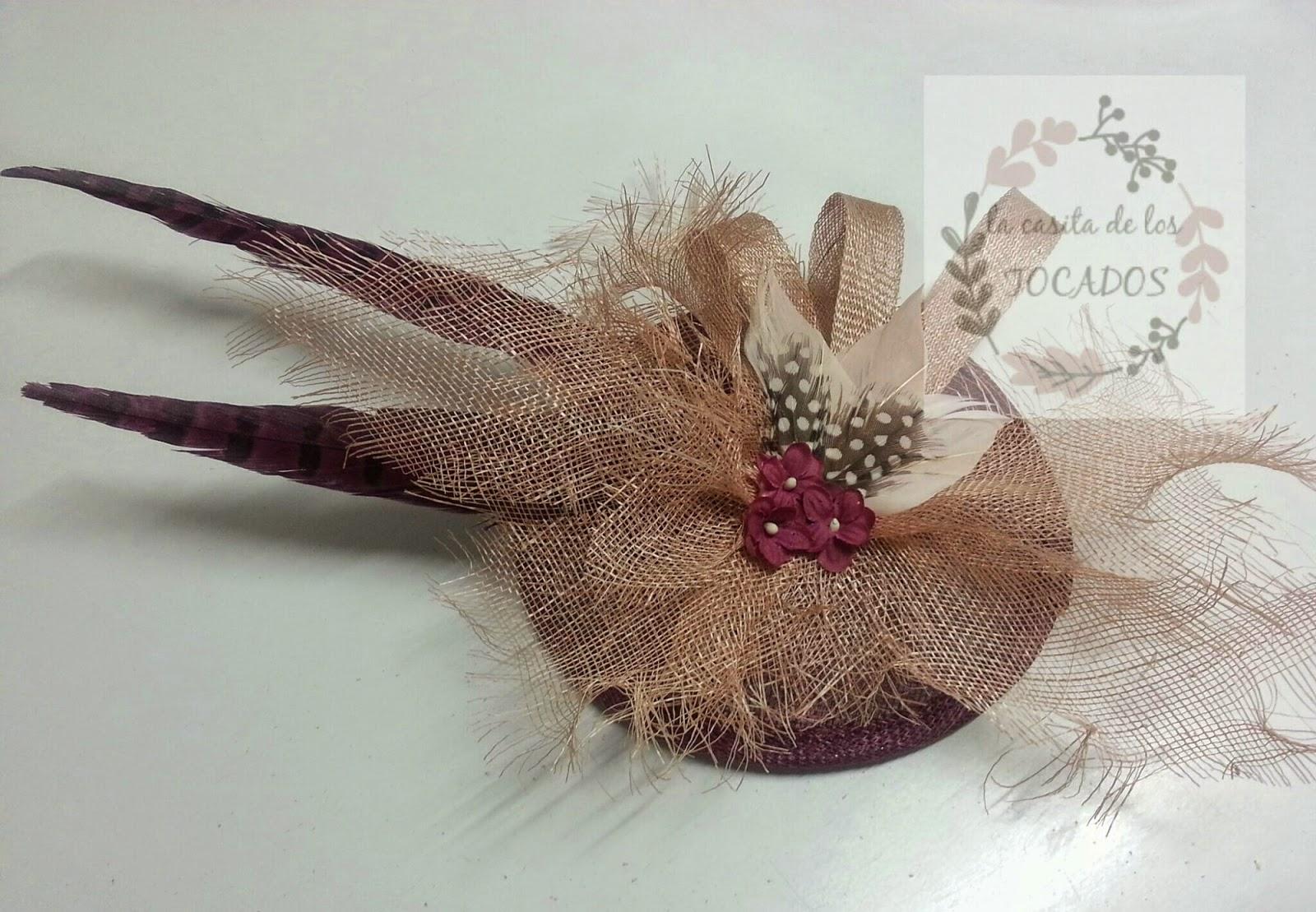 tocado con base redonda de sinamay, plumas variadas y sinamay deshilachado en colores vino y nude
