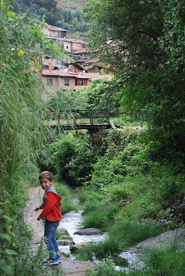 Niño con chaqueta roja a orillas de un río con el pueblo al fondo
