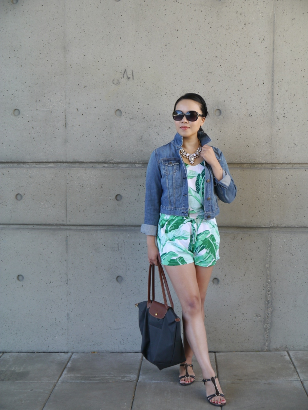 Casual summer style: palm print romper, denim jacket, white statement necklace. oversize sunnies