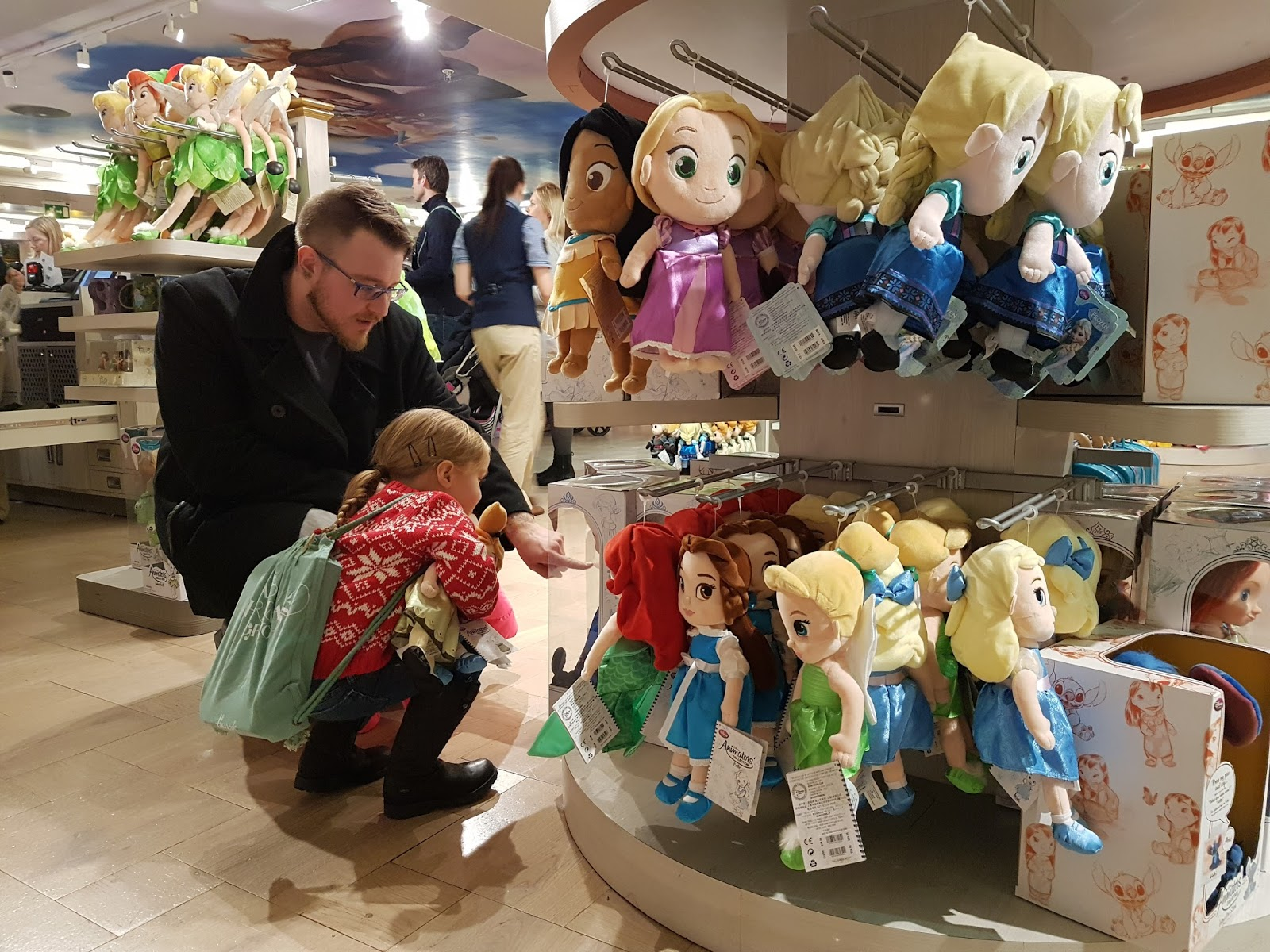 girl choosing a toy with dad at disney store