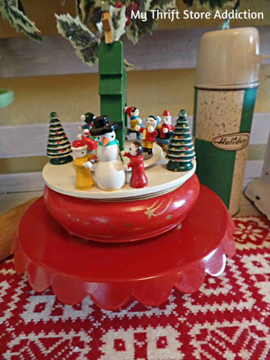 A Holly Jolly Jadeite Kitchen mythriftstoreaddiction.blogspot.com A thrift store music box displayed on a cake stand  with holiday decor
