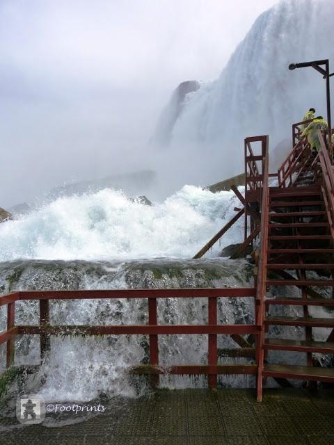 Inzwischen ist das rauschen des Wasserfalls in ein Tosen uebergegegangn. Hier hat man das Gefühl mitten in den Niagarafaellen zu stehen. Das Wasser rauscht uns um die Füsse und jetzt wuenschte ich mir doch, die Badelatschen angezogen zu haben.  Wassernebel umgibt uns und wir werden nass trotz des Umhangs, yeah, duschen inmitten der Niagarafaelle ist ein einmaliges Erlebnis!