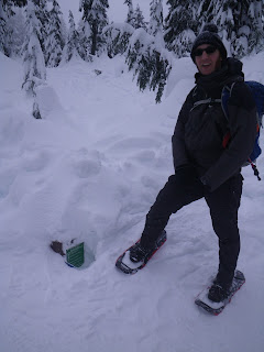 A person standing next to a sign post buried in the snow.  The placard with trail names has been dug out of the snow and is at ankle height to the person.