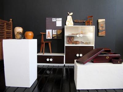 Modern dolls' house miniature gallery, showing various wooden furniture and homeware pieces displayed on plinths, in a glass-fronted  cupboard, and on the wall.