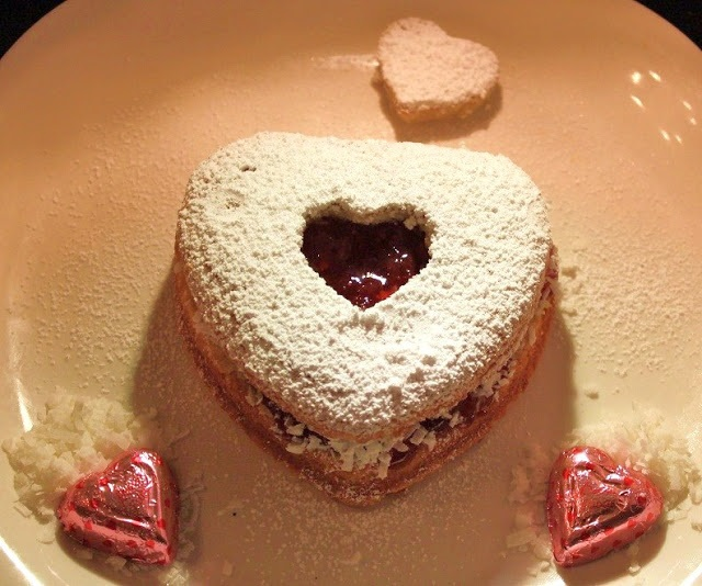 this is a homemade heart shaped cake filled with Red Raspberry Jam and coconut then sprinkled with powdered sugar for Valentines Day