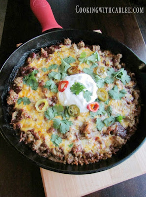 cast iron skillet full of tamale pie and toppings
