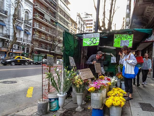 Un puesto de flores en la Capital y Una joven comprando.