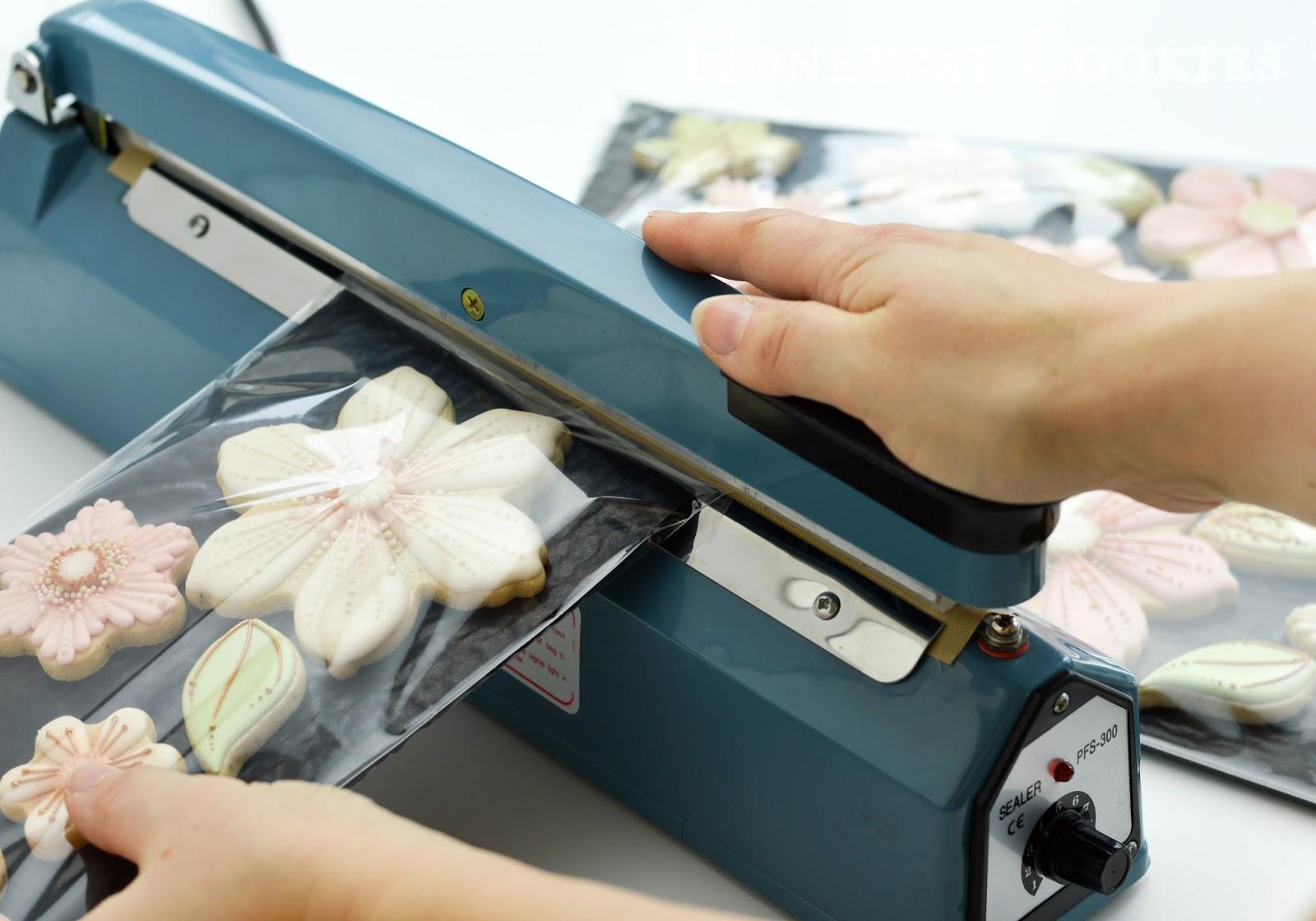 Shot of heatsealer in action sealing up layers of flower cookies, by Honeycat Cookies.