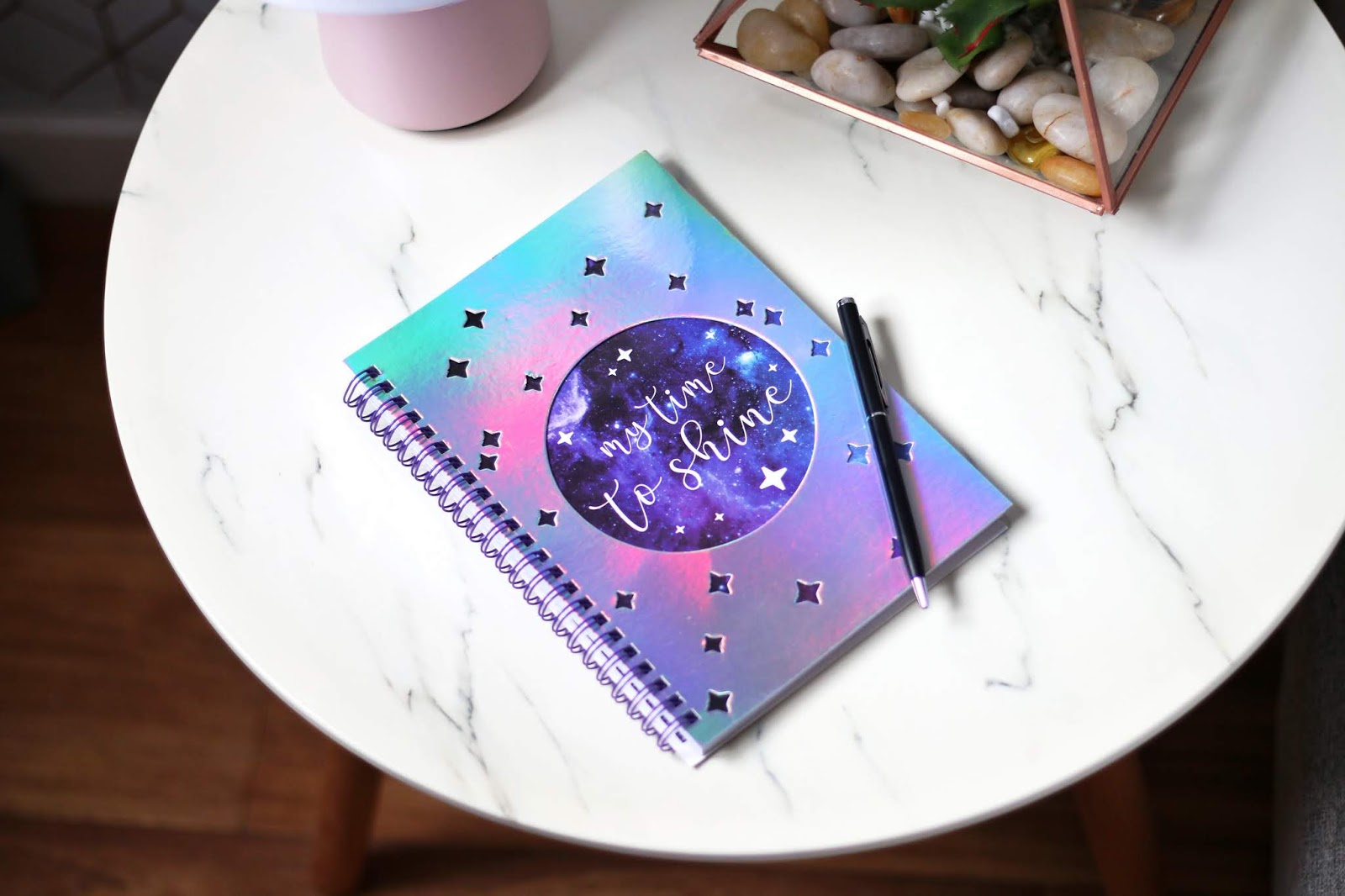 Close up photo of a silver and purple notebook on a white marble side table