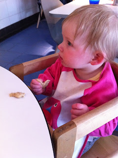 A baby eating a breadstick in Pizza Express with a long sleeve bib on and in a high chair