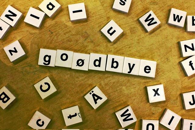 scrabble tiles spelling goodbye surrounded by random tiles